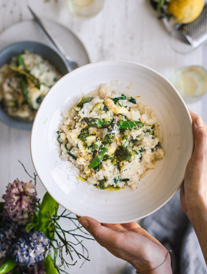 Holding a plate of creamy asparagus risotto with wild garlic pesto