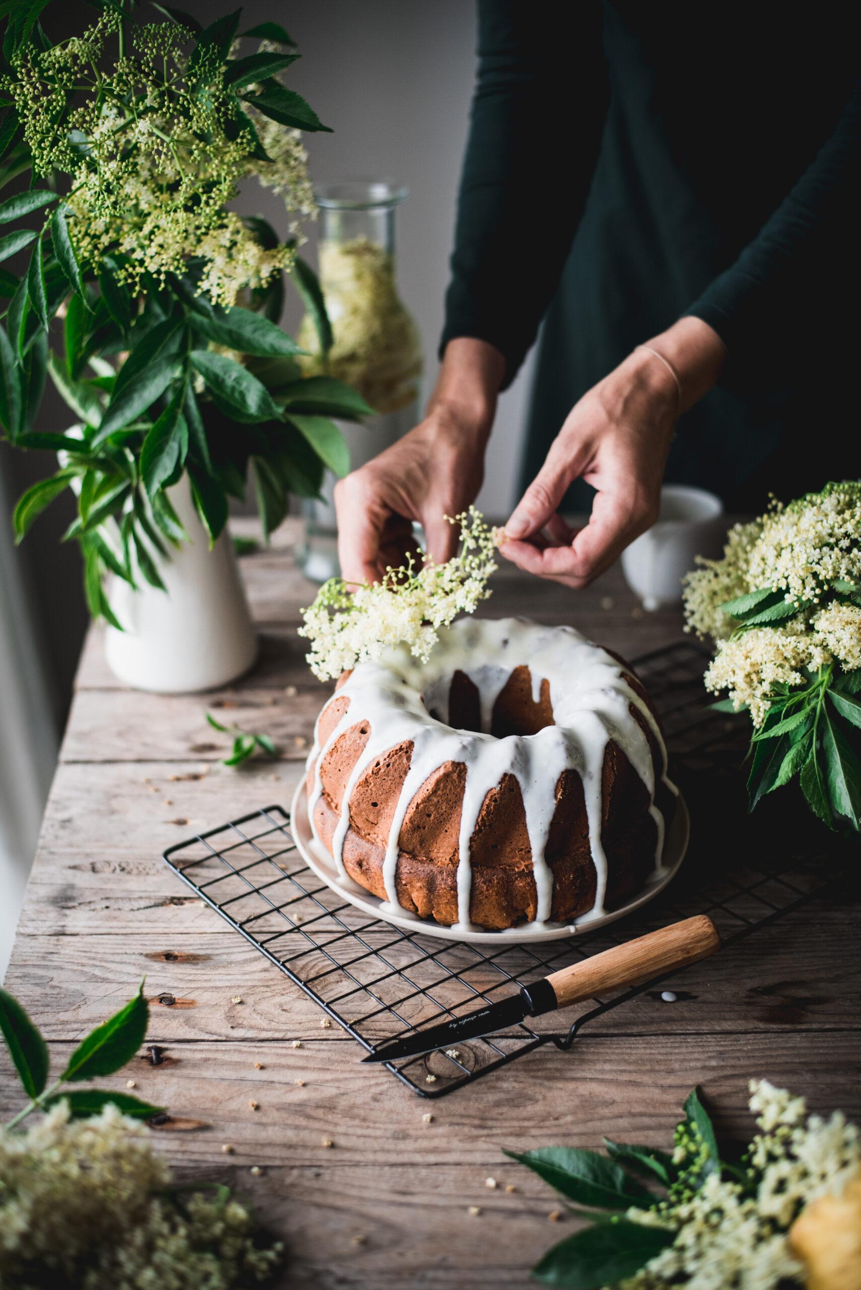 Decorating a delicious Elderflower Bundt Cake with more Elderflowers
