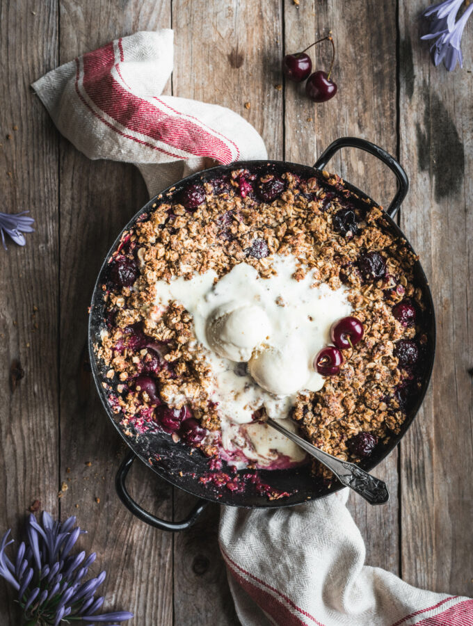 A baking dish with juicy, warm cherries topped with a crispy oat crumble