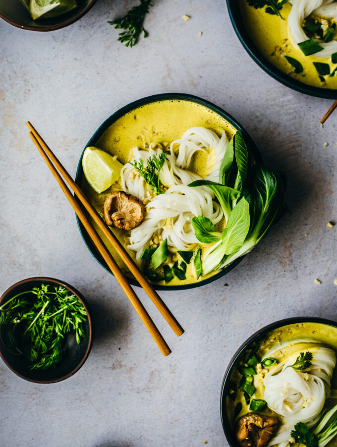 A bowl of creamy yellow curry soup with ricenoodles & green veggies